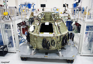 Technicians prepare to fit a special fixture around an Orion capsule inside the high bay of the Operations & Checkout Building at NASA's Kennedy Space Center in Florida. Original from NASA. Digitally enhanced by rawpixel.