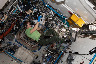 Astronaut Anne McClain of NASA peers into a microscope | by NASA Johnson