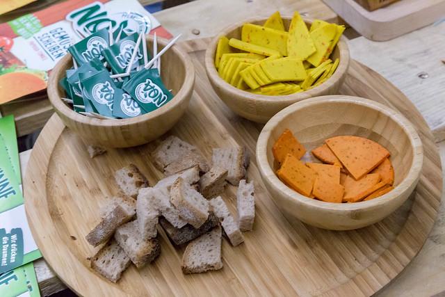 Vegane Käseproben in Schälchen aus Holz mit Brot auf einem Brettchen