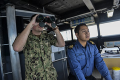Lt. j.g. Ben Ralen and Lt. j.g. Akmal Japin search for surface contacts on the bridge of USNS Fall River (T-EPF 4) during CARAT tactical maneuvering drills. (U.S. Navy/MC1 Greg Johnson)