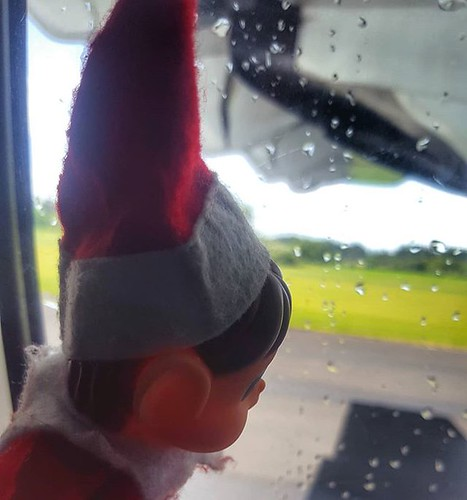 #elfjourney #adventure Image description: Excited Christmas elf looking out of aeroplane window as plane taxis along runway. | by easegill