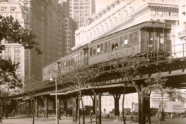 Just a few blocks south from Wall Street, unemployed men wander around Battery Park during the Great Depression. The old 9th Avenue Elevated Railroad slices right through the park at the very southern tip of Manhattan. New York. 1933