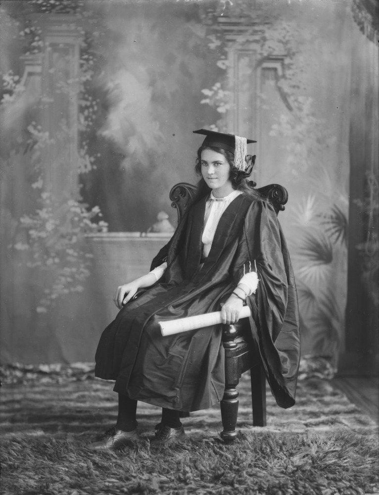 Woman in graduation gown holding a diploma