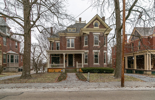 house dwelling residence historic paris kentucky unitedstatesofamerica us twostory brick queenanne bourboncounty sidewalk street hedges shrubbery bushes trees spandrels polygonalbay shingled shingles roundarched modillions columns voussoirs ca1895 fischer