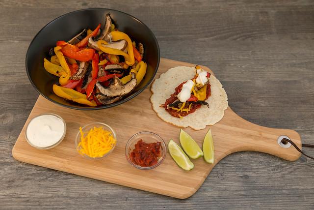 Hellofresh - Vegetarische Fajitas mit Paprika & Pilzen selbst gemachter, scharfer Soße und Limettenschmand auf einem Brettchen