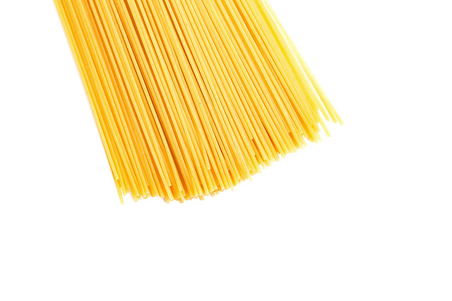 Top view of dry spaghetti pasta on white background