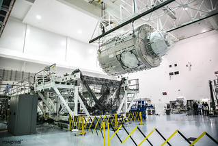 In the Space Station Processing Facility at NASA's Kennedy Space Center in Florida, operations are underway to place the International Space Station's Node 3, named Tranquility, into a payload transportation canister for its move to Launch Pa
