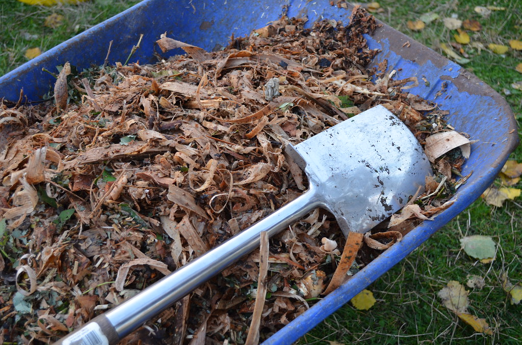 Wheelbarrow with mulch and spade