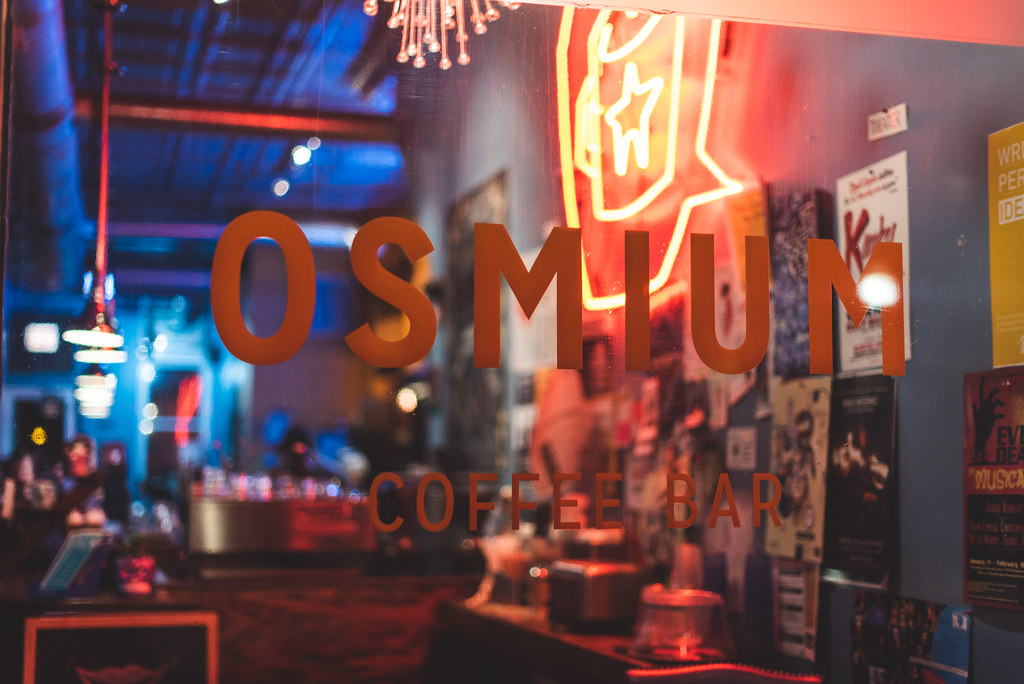 The window of a coffee bar, neon light shining from inside.  The sign reads Osmium.