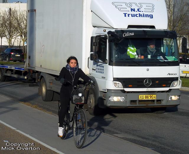 Pretty girl rides a bike on a cold December Copenhagen day