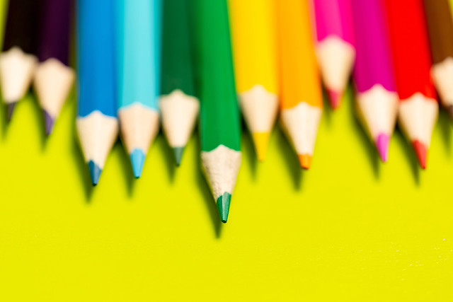 Multicolored pencils on a yellow