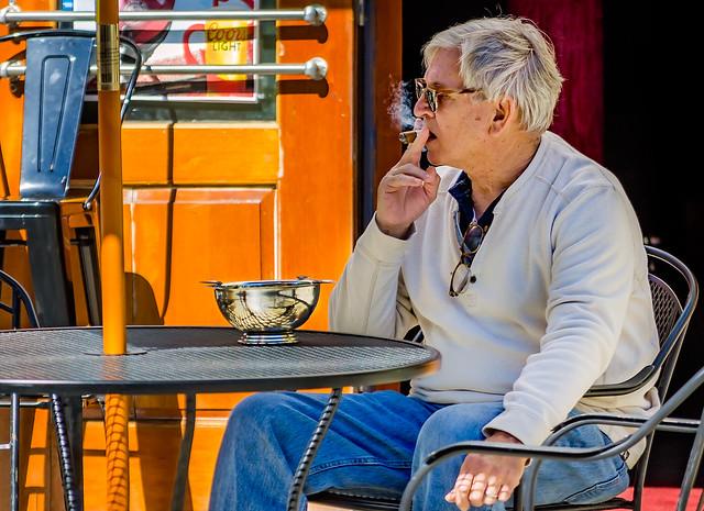 Man smoking cigar outside Lit Cigar Lounge on Dauphin Street in downtown Mobile Alabama