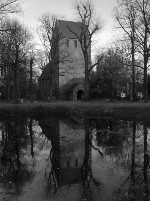 Schwarzweißfoto: Die Dorfkirche Marienfelde zwischen ein paar kahlen Bäumen spiegelt sich in einem Weier