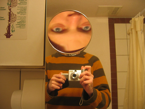 White person with blue eyes and a Freddie Krueger sweater taking a selfie in a mirror,  except a smaller circular mirror is inverting their face where their head would usually be.