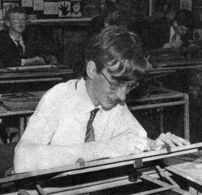 Grainy black-and-white photo of me in a school shirt and tie drawing on a drawing board