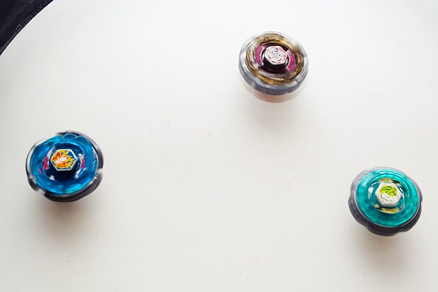 Trio Beyblades spinning at the home made stadium