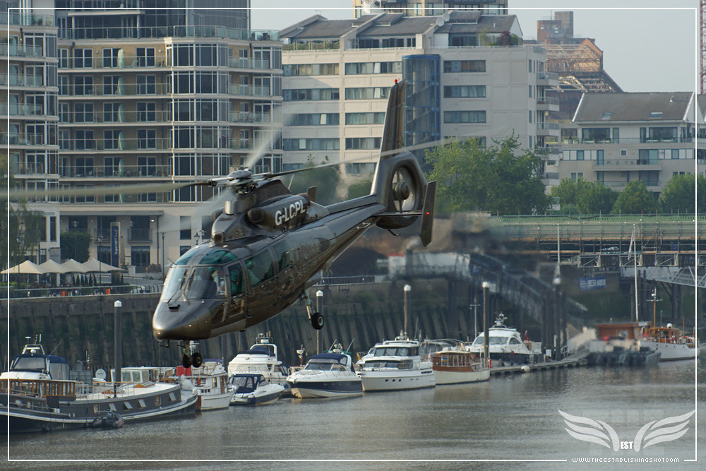 The Establishing Shot: OBERHAUSER'S HELICOPTER FROM SPECTRE TAKING OFF WITH BOND'S SPECTRE BOATS IN THE BACKGROUND G-LCPL AEROSPATIALE SA365N2 DAUPHIN 2 - LONDON