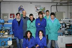 En la imagen se muestra a un grupo de alumnos/as en uno de los talleres del centro posando junto a su profesor.