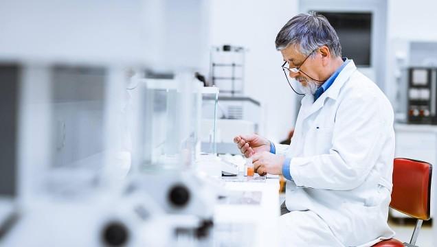 Man in white lab coat using scientific equipment