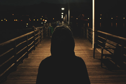 Silhouette of Person in Hoodie on Boardwalk at Night | by Image Catalog