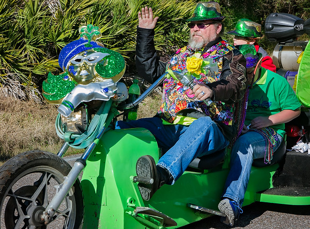 A biker waves in the People's Parade during Mardi Gras in Dauphin Island, Alabama
