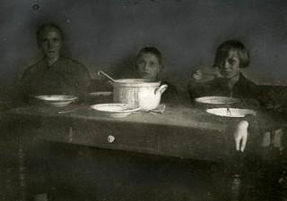 Arm arbeidersgezin aan de maaltijd / Poor miners' family eating soup