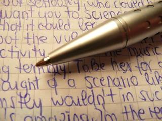 Metallic ballpen tips / biro Ballpen Ballpoint pen in silver with handwritten random blue text on quad-ruled paper   by photosteve101
