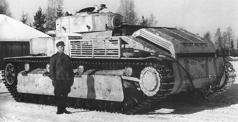 Finnish tanker is photographed standing next to a captured Soviet T-28 tank