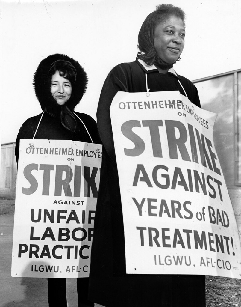 An Asian American and an African American woman wear signs that indicate that they are on strike against Ottenheimer for poor treatment and unfair labor practices, December 1, 1966.