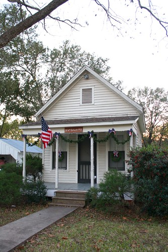 sunset architecture wooden texas garland historic christmaslights wreaths frontporch screendoor usaflag smalltowns harriscounty windowscreens tomballtx countrydoctor texasscenes tomballmuseumcenter christmascandlelighttour countrydoctorsoffice drwmehrhardtmd patrioticchristmasdecorations