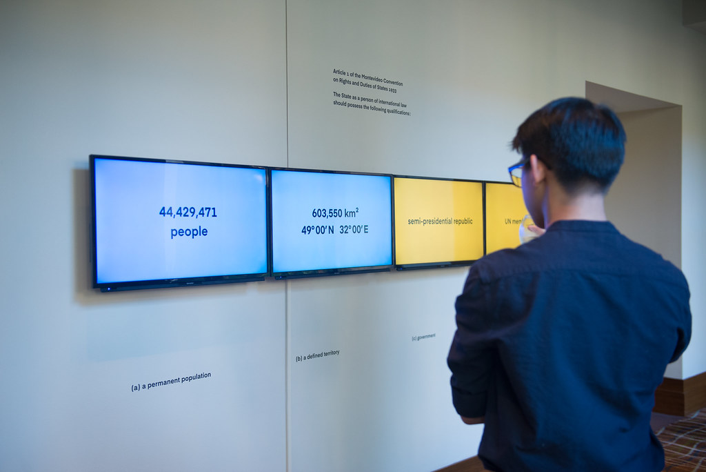 person looking at video monitors on wall