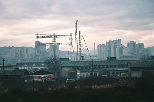 city sunset industry clouds train europe crane sarajevo bosnia rail railway plattenbau electricity suburb balkans murky warehouses highrises sheds towerblocks banlieue bosna passingby novosarajevo southeasteurope southeasterneurope byrail
