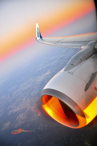above sunset window plane glow view florida seat horizon wing jet engine airline winglet westjet