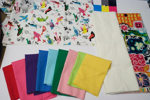 I'll fussy-cut the birds, and surround them with different solids. The bird fabric isn't a bright white, but instead more of a warm-toned white, so I grabbed a warm white to use for white space. The bright, busy fabric on the right is the quilt backing.