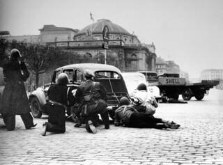 Frihedskæmpere i dækning bag biler på Kongens Nytorv i København under skudkamp med HIPO-folk d. 5. maj 1945. I baggrunden ses Det kongelige Teater