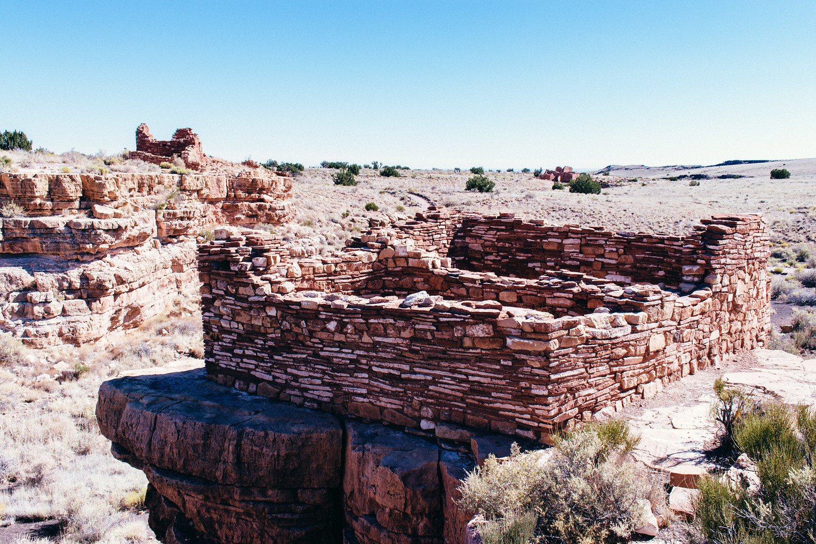 Square-shaped ruins perched on the edge of a shallow canyon rim