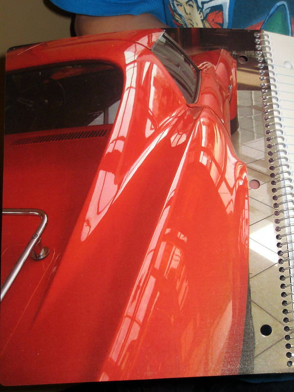 Inside front cover of a spiral-bound notebook with 4 photos of a 1970 Corvette