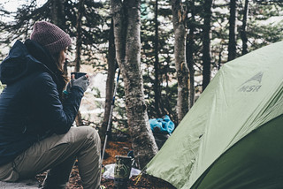 Female Camper Drinking from Cup by Tent | by Image Catalog