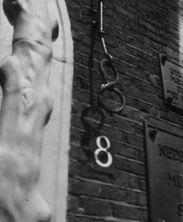 """De deurbel in de vorm van een krakeling. Het pand heeft nogal wat verschillende huisnummers gehad. Een bord bij de ingang geeft een citaat uit 1668 van Everard Meijster: """"Uterech; .... zij is de parel van Euroop,"""" Coll. Het Utrechts Archief."""