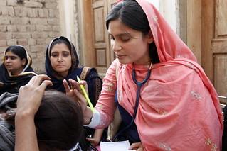A female doctor with the International Medical Corps examines a woman patient at a mobile health clinic in Pakistan | by DFID - UK Department for International Development