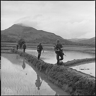 Men of H Company, 2nd Battalion, 7th Marines, move along rice paddy dikes in pursuit of the Viet Cong: 12/10/1965