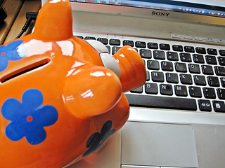 Piggy Bank Looking at Laptop | by Images_of_Money