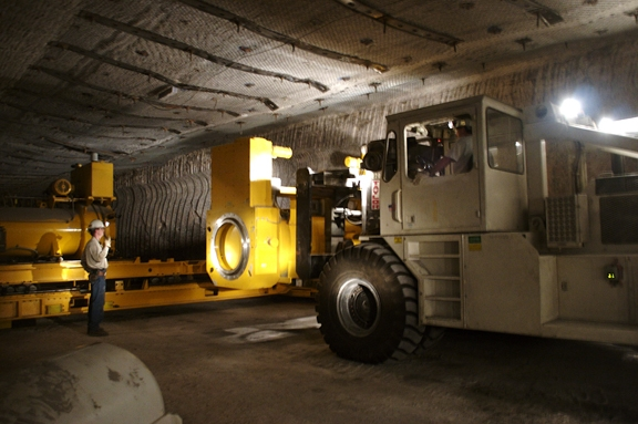 A beige specialty vehicle moves industrial equipment in a windowless space while a male-presenting person in a white hardhat and beige workwear looks on.