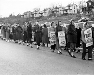 Pickets march in line in a suburban area announcing their support for the union. | by Kheel Center, Cornell University Library