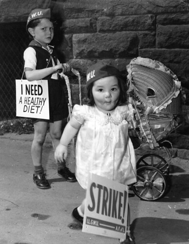 """Two young children push a dolls carriage and carry signs in support of their parents' strike.  Their signs read """"Strike!"""" and """"I Need a Healthy Diet!"""" 