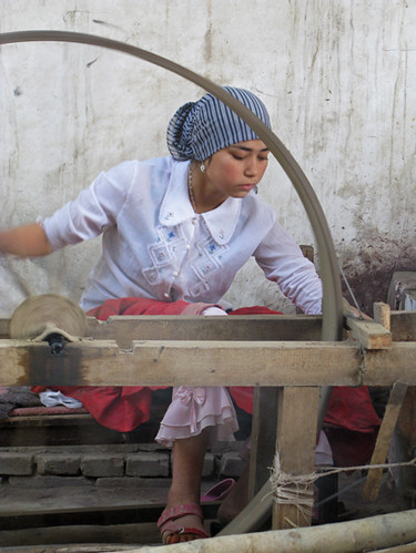 Girl spins freshly extracted silk - Hotan, Xinjiang | by retrotraveller