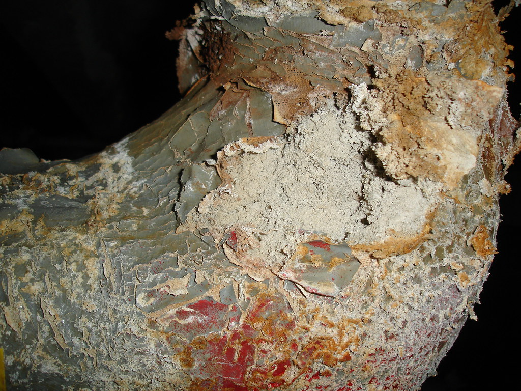 Damaged Asbestos Insulation on Pipe Elbow | Perhaps one may