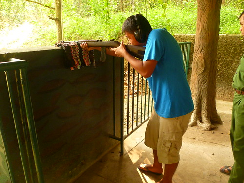 Shooting a rifle in Cu Chi Tunnels in Vietnam   by JMParrone