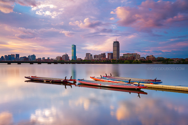 Boston Skyline and Charles River Dragon Boats, Cloudy Sunrise over Back Bay and Harvard Bridge with Mirror Reflection from Cambridge MA USA