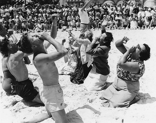 American golfers doing the Hokey Pokey on a sandy beach, Coolangatta, Gold Coast, 1953